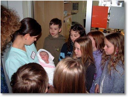 DIe Schüler der Klasse 4 Sonnenschule bei einem Neugeborenen