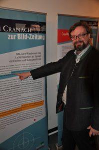 Professor Dr. Albrecht Geck erläutert anhand einer Bildtafel die Aufgabe der von ihm konzipierten Ausstellung, die zur Zeit in der Erlöserkirche in Attendorn zu sehen ist. Foto: Karl-Hermann Ernst